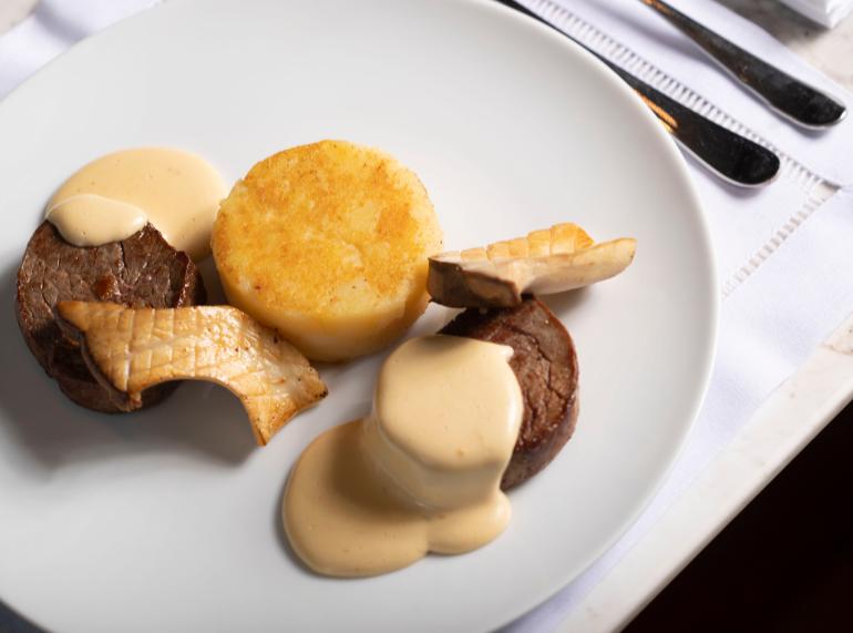 Prato com dois medalhões de carne com creme por cima, cogumelos e batata prensada em formato arredondado semelhante aos medalhões de carne.