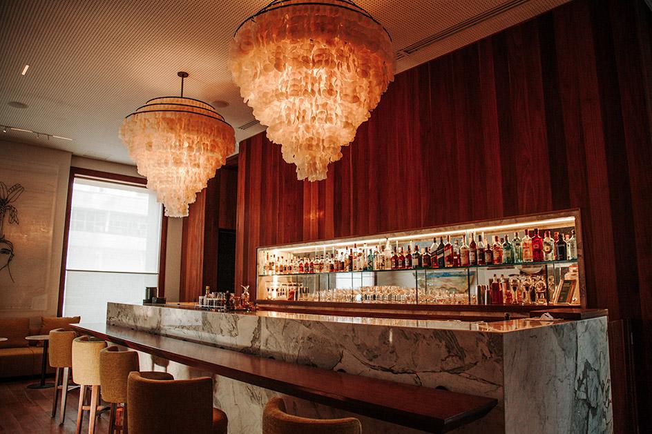 Piano bar com dois lustres de escama de peixe, prateleiras de bebidas, balcão de granito, bancada de madeira e cadeiras altas.