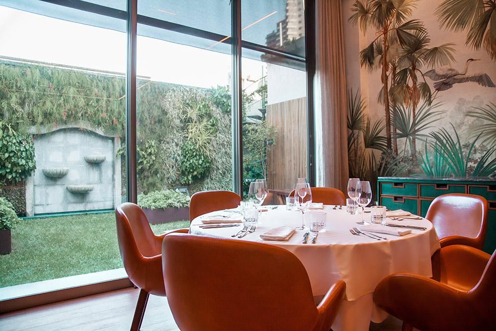 Mesa posta com taças, talheres e toalha de mesa. Ao redor, seis cadeiras. Ao fundo, mural artístico que representa um mangue e um quintal.