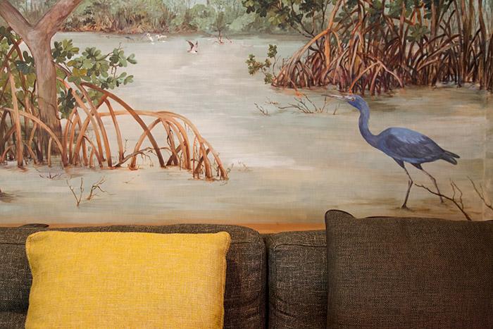 Fotografia de um sofá marrom, com uma almofada amarela, afrente do mural artístico que representa um mangue com uma garça azul.