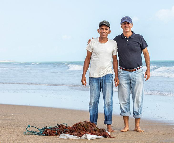 Fotografia do Chef Proprietário André Bichucher ao lado de um pescador, em frente ao mar.