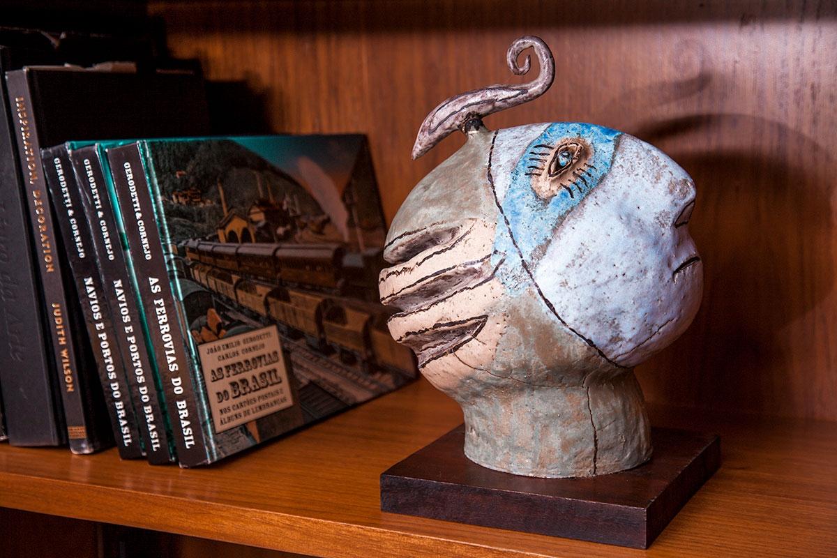 Fotografia de uma prateleira de livros. Ao lado livros inclinados e com maior foco uma obra em argila com formato de um rosto indígena.