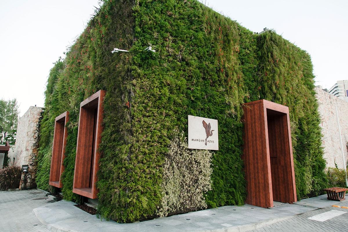 Fotografia da fachada do restaurante Mangue Azul que destaca seu paisagismo criado com plantas naturais. Destacam-se uma pedra com a marca e as janelas e portas de madeiras.