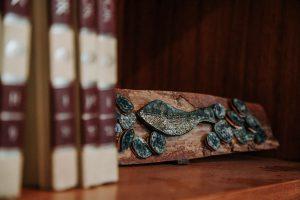 Fotografia de uma prateleira de livros com uma obra que remete a um peixe aplicado em uma madeira retangular.