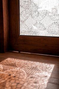 Porta de vidro com renda renascença com sol de fora pra dentro, gerando sombras no piso de madeira.
