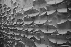 Foto preto e branca de uma parede com formatos tridimensionais que remetem ao mar, peixe e praia.