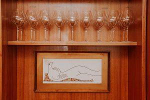 Uma obra em desenho a baixo de uma prateleira de taças que representa formas de uma mulher deitada.